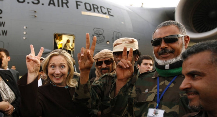 Then-Secretary of State Hillary Clinton poses with Libyan fighters in October 2011.
